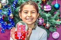 Petite fille recevant le globe de neige avec amour pour des repres de Noël Photographie stock libre de droits