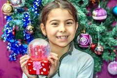 Petite fille recevant le globe de neige avec amour pour des repres de Noël Photographie stock