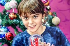 Petite fille recevant le globe de neige avec amour pour des repres de Noël Image libre de droits