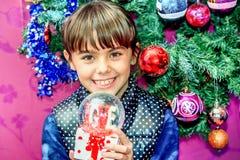 Petite fille recevant le globe de neige avec amour pour des repres de Noël Photo stock