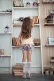 Petite fille recherchant le livre dans la bibliothèque ; Image stock