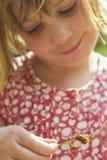 Petite fille regardant Caterpillar sur la lame de l'herbe Photographie stock libre de droits