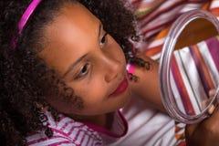 Petite fille regardant elle-même dans un miroir Images stock