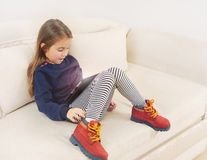 Petite fille regardant fixement dans la stupéfaction le dispositif de comprimé, technologie Co Images libres de droits