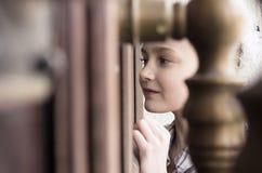 Petite fille regardant la fenêtre de porte de jet Photos stock