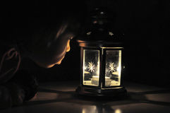 Petite fille regardant la lumière de bougie dans la lanterne, OIN élevée photos stock