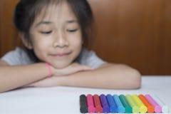 Petite fille regardant la pâte à modeler colorée Image stock