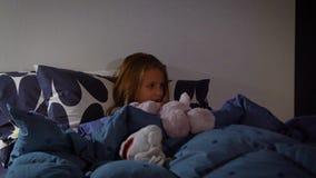 Petite fille regardant la TV dans son lit avant d'aller dormir, foyer sélectif banque de vidéos