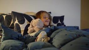 Petite fille regardant la TV dans son lit avant d'aller dormir, foyer sélectif clips vidéos