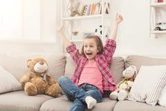 Petite fille regardant la TV tout en se reposant sur le sofa Photographie stock libre de droits