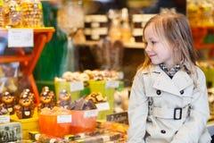Petite fille regardant le chocolat dans la boutique photographie stock libre de droits