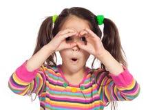 Petite fille regardant par binoche imaginaire photo stock