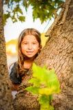 Petite fille regardant par derrière l'arbre photo stock