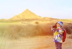 Petite fille regardant par des jumelles en montagnes Photographie stock libre de droits