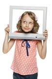 Petite fille regardant par le cadre d'écran de TV/ordinateur Image stock
