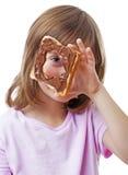Petite fille regardant par un pain avec du beurre de chocolat Image libre de droits