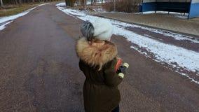 Petite fille regardant pour traverser la rue et puis pour aller à l'arrêt d'autobus banque de vidéos