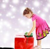 Petite fille regardant un cadeau Image libre de droits