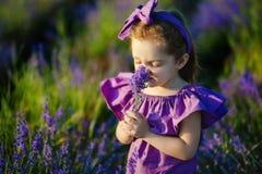 Petite fille reniflant le parfum de la fleur bleue photos stock