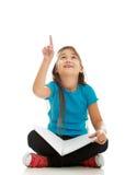 Petite fille reposant à jambes croisé et l'étude Image stock