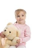 Petite fille retenant un ours de nounours Image stock