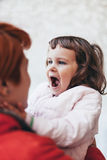 Petite fille riant de sa mère photo stock