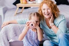 Petite-fille riante prenant des photos avec sa grand-mère Images stock