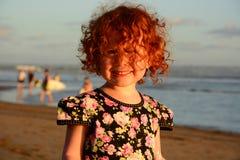 Petite fille rousse mignonne heureuse sur la plage de Bali Coucher du soleil Photographie stock libre de droits
