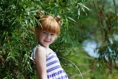 Petite fille rousse mignonne posant près de l'arbre photos stock