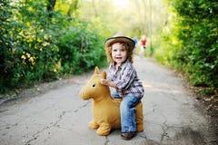 Petite fille rousse montant un cheval de jouet image stock