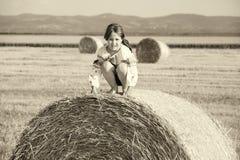Petite fille rurale sur la paille après champ de récolte avec BAL de paille Photo stock