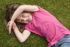 Petite fille s'étendant dans l'herbe image stock