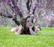 Petite fille s'étendant dans l'herbe Photo stock