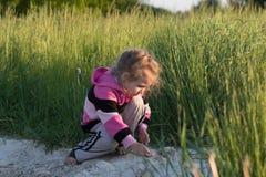 Petite fille s'accroupissante jouant en saleté de champ dehors au contexte vert naturel d'herbe de pré Photos libres de droits