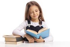 Petite fille s'asseyant à une table et lisant un livre Image stock