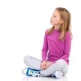 Petite fille s'asseyant avec des jambes croisées Images libres de droits
