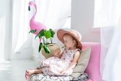 Petite fille s'asseyant avec la lucette sur l'entraîneur dans le salon à la maison avec le chapeau Images libres de droits