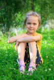Petite fille s'asseyant dans l'herbe Photographie stock