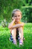 Petite fille s'asseyant dans l'herbe Photographie stock libre de droits
