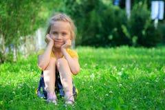 Petite fille s'asseyant dans l'herbe Photo libre de droits