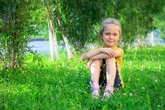 Petite fille s'asseyant dans l'herbe Image stock