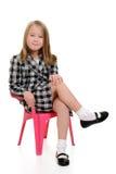 Petite fille s'asseyant dans la chaise rose Photographie stock