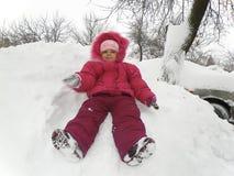 Petite fille s'asseyant dans la neige Photo libre de droits