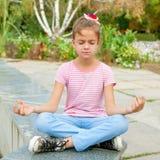 Petite fille s'asseyant dans la pose de yoga Images stock