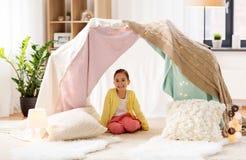 Petite fille s'asseyant dans la tente d'enfants à la maison Images libres de droits