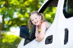 Petite fille s'asseyant dans la voiture blanche Photos stock