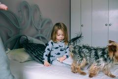 Petite fille s'asseyant dans le lit images stock