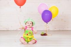Petite fille s'asseyant dans le studio avec des boules photo libre de droits