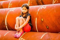 Petite fille s'asseyant dans le tuyau images libres de droits
