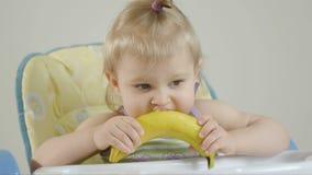 Petite fille s'asseyant dans une chaise de bébé mangeant une banane banque de vidéos